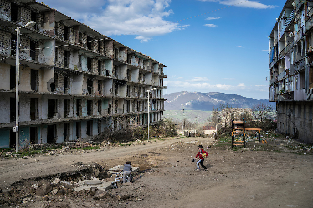 SHUSHI, NAGORNO-KARABAKH - APRIL 18: Boys play on a street next to a building destroyed by war more than twenty years earlier on April 18, 2015 in Shushi, Nagorno-Karabakh. Since signing a ceasefire in a war with Azerbaijan in 1994, Nagorno-Karabakh, officially part of Azerbaijan, has functioned as a self-declared independent republic and de facto part of Armenia, with hostilities along the line of contact between Nagorno-Karabakh and Azerbaijan occasionally flaring up and causing casualties. (Photo by Brendan Hoffman/Getty Images) *** Local Caption ***