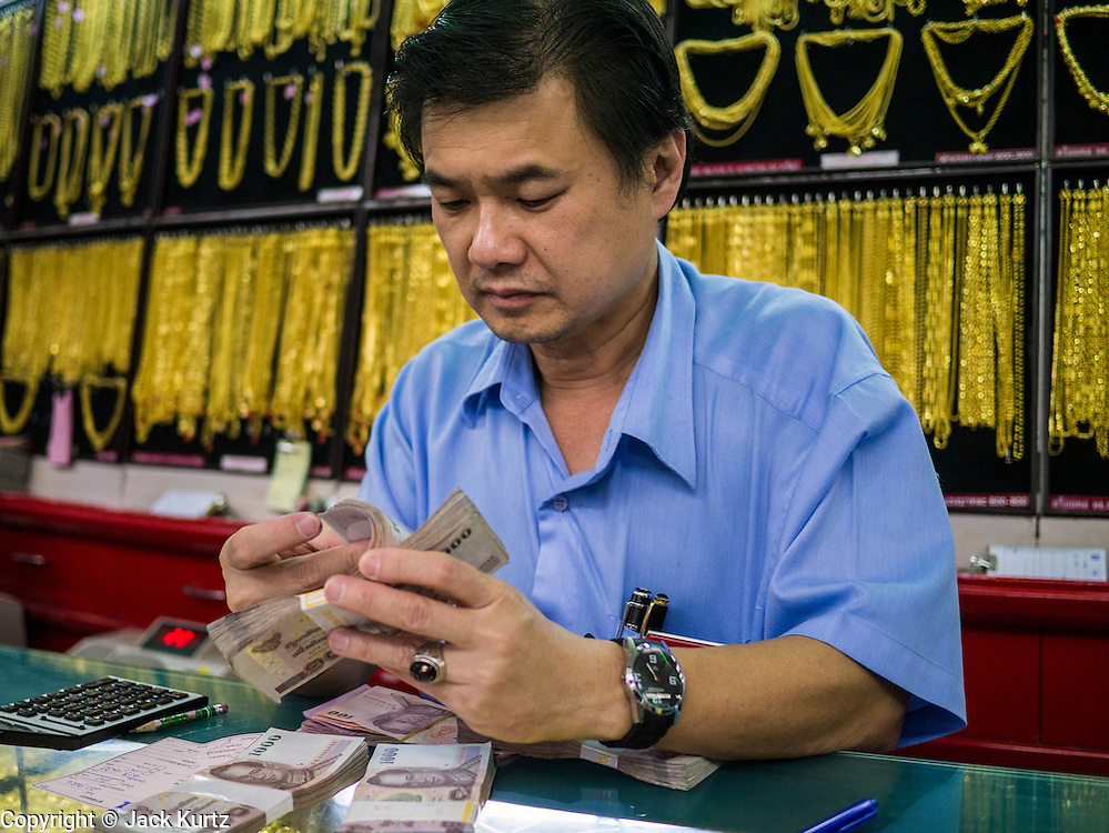 10 SEPTEMBER 2013 - BANGKOK, THAILAND: A worker counts cash received from a customer buying gold in a gold shop in the Chinatown section of Bangkok. Thais buy gold as both jewelry and an investment, a hedge against inflation and financial failures. Chinatown is the center of the gold trade in Thailand.     PHOTO BY JACK KURTZ
