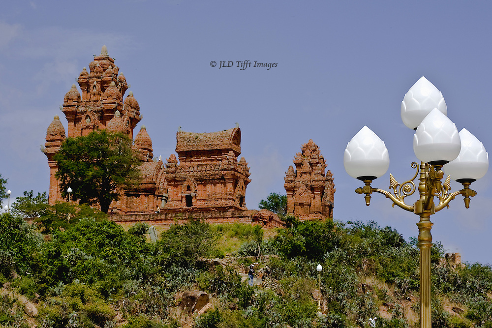 On a hill near Phan Rang, South Vietnam, the Cham towers of Po Klong Garai, seen from a new parking lot lit by street lamps whose shapes echo the shape of the brick towers.  The group of small Hindu temples are still used for worship by Vietnamese Buddhists as well as Cham descendants.  They are built of brick without mortar.