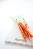 Freshly washed carrots on a white plastic chopping board.