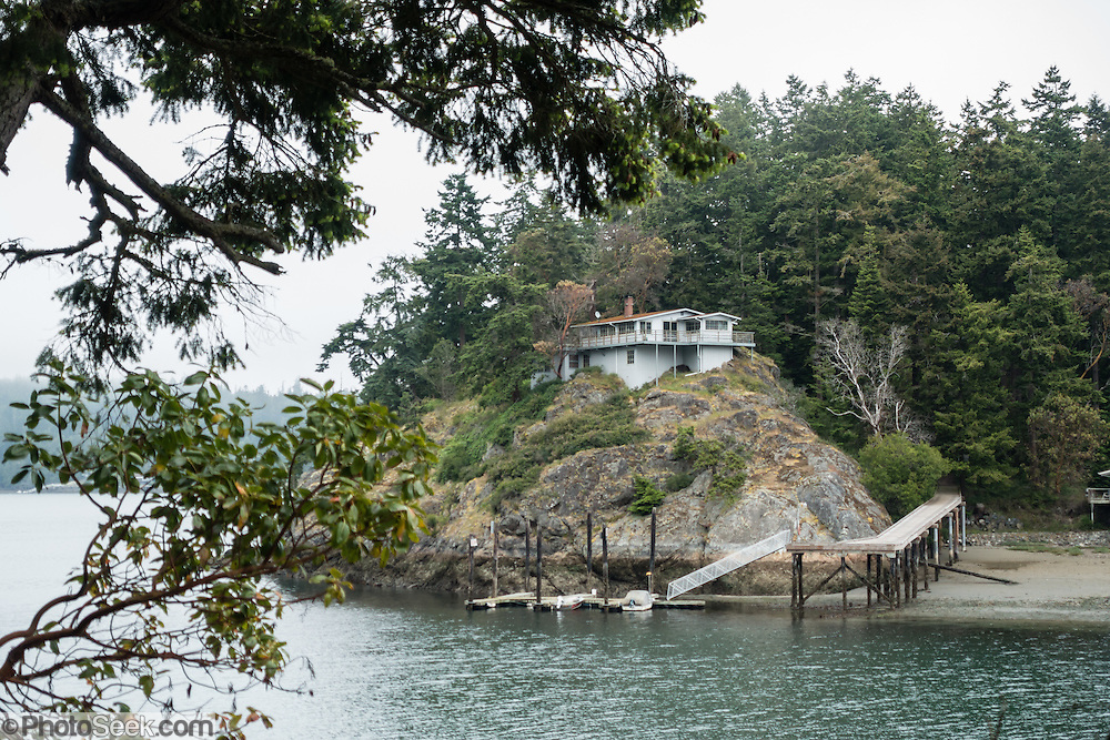 "Surrounded by the salty waters of Deception Pass, this remote house on Ben Ure Island can only be reached via boat. Aside from several private properties such as this, most of Ben Ure Island is within Deception Pass State Park, in Washington, USA. Elsewhere on the island, you can rent a quiet State Park cabin. Photographed from the park's scenic Goose Rock Perimeter Trail on Whidbey Island. In the late 1880s, Ben Ure and his partner Lawrence ""Pirate"" Kelly ran a profitable but illegal business smuggling Chinese immigrants for local labor. Local stories say he would hide the immigrants wrapped in burlap bags which could be tossed overboard if US Customs agents were encountered. Tidal currents would carry the immigrants' bodies northwest to San Juan Island to what became known as Dead Man's Bay -- now called Deadman Bay, bordering Lime Kiln Point State Park. Deception Pass is a strait of water separating Whidbey Island from Fidalgo Island, and connects Skagit Bay (part of Puget Sound) with the Strait of Juan de Fuca, which are all part of the Salish Sea. Deception Pass is the most-visited State Park in Washington."