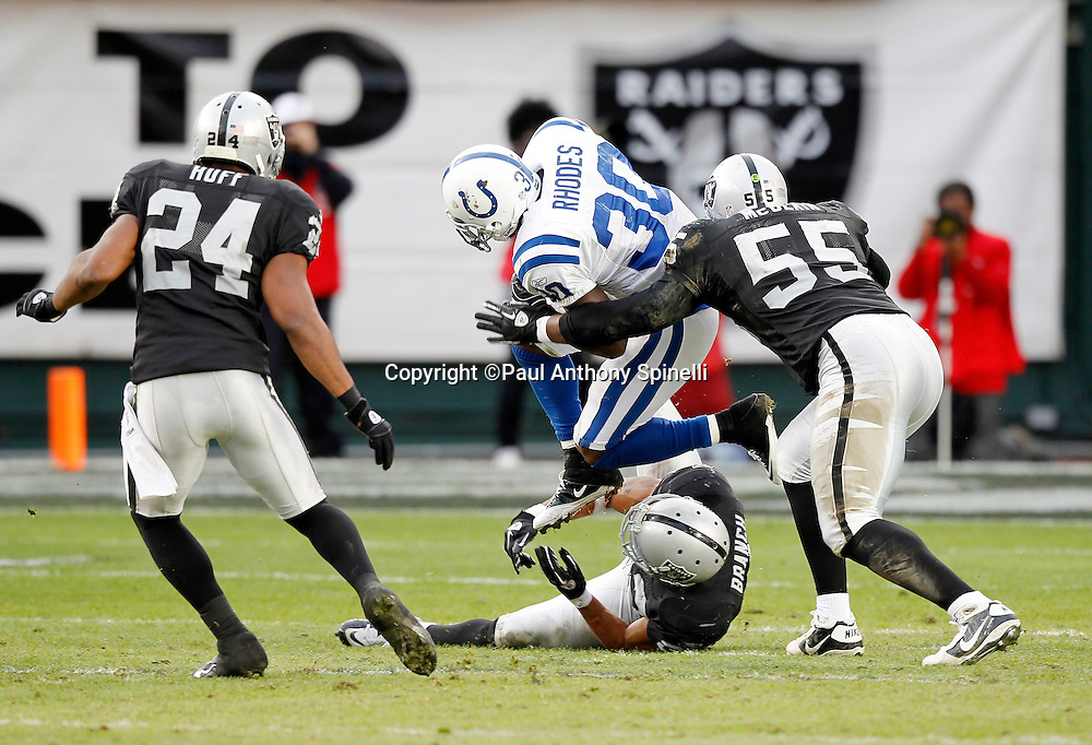 Indianapolis Colts running back Dominic Rhodes (30) jumps over Oakland Raiders safety Tyvon Branch (33) as Oakland Raiders linebacker Rolando McClain (55) closes in on a tackle during the NFL week 16 football game against the Oakland Raiders on Sunday, December 26, 2010 in Oakland, California. The Colts won the game 31-26. (©Paul Anthony Spinelli)
