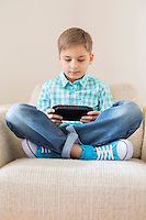 Boy playing hand-held video game on sofa at home