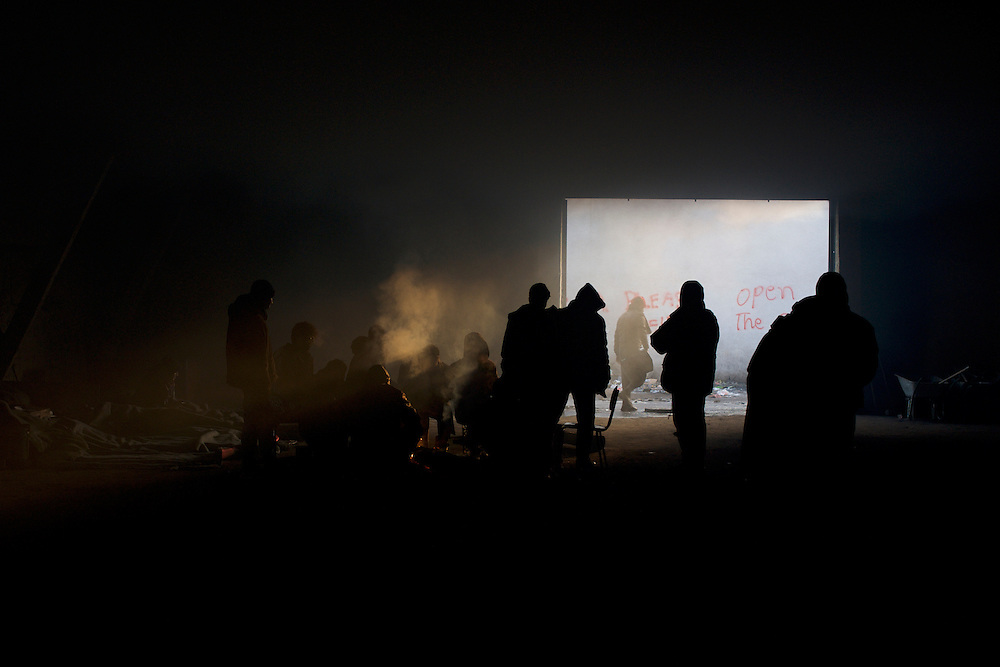 A group of migrants socialise covered with smoke around a open fire inside a makeshift shelter near Belgrade's main railway and bus stations.