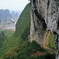 Rocky Lok climbs the unusual overhanging limestone arch of Moon Hill, Yangshuo, Guilin, China