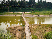 11 MARCH 2016 - LUANG PRABANG, LAOS: The bamboo foot bridge across the Nam Khan River near Luang Prabang. The bridge is seasonal. Villagers put it up every year, at the at the start of the dry season and take it down when the Nam Khan floods during the rainy season.  Laos is one of the poorest countries in Southeast Asia. Tourism and hydroelectric dams along the rivers that run through the country are driving the legal economy.     PHOTO BY JACK KURTZ