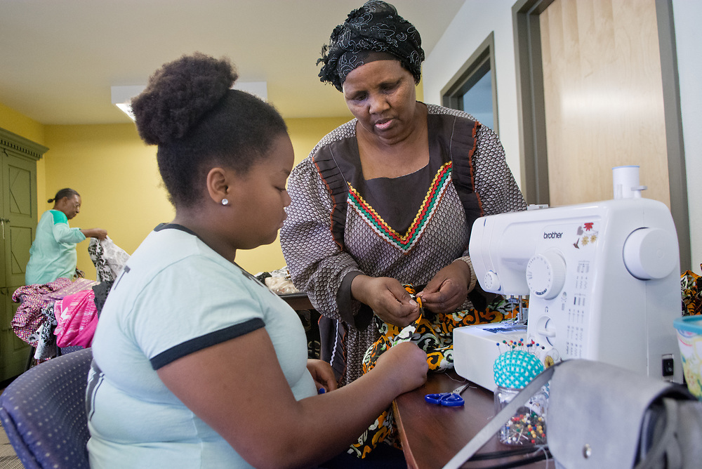 mkb070717g/metro/Marla Brose/070717 -- Tali Sinandile, 12, works with her grandmother Nkazi Sinandile to sew a  kitenge, a wrap-around skirt, while working with other girls to create clothing for an upcoming fashion show and choir performance of refugee children from Africa. o from Mozambique, will model in the fashion show. The show will be at the African American Performing Arts Center on July 16 at 4 p.m. Tickets will be available at the show.(Marla Brose/Albuquerque Journal)