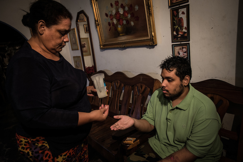 "MARACAY, VENEZUELA - JULY 4, 2016: Evelin RodrÍguez gives partial doses of medicine to her two schizophrenic sons, Gerardo and Accel. It is difficult to care for them in Venezuela - a country suffering from severe shortages of medicines, including the psychiatric drugs that she needs to keep her sons' conditions stabilized. It is an exhausting task taking care of them and going from pharmacy to pharmacy for hours searching for the medicines that her sons need, that she is rarely able to find. She copes by reducing their doses, and by sharing their prescriptions depending on which son needs the medicine the most each day. Evelin is a lawyer, but has quit all of her work since Accel attempted to cut off his arm after three weeks without his medicine. Evelin now spends her days looking after Accel and Gerardo, too afraid to leave them alone because they might hurt themselves.  ""I am tired,"" she said. ""This is too much sometimes"". PHOTO: Meridith Kohut for The New York Times"
