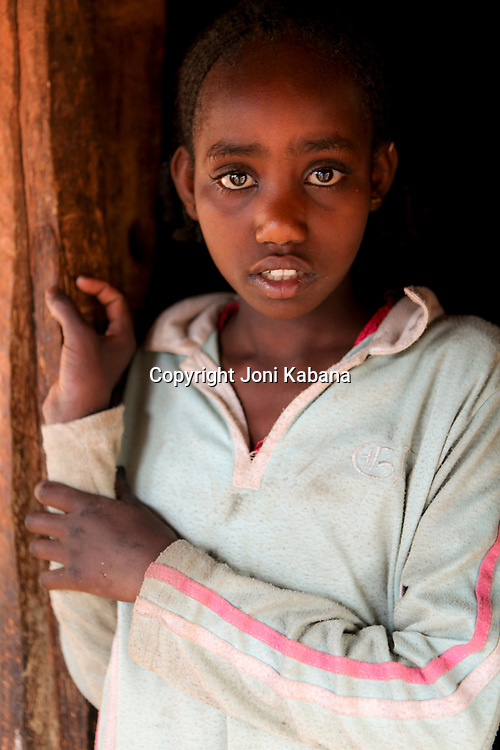 A young girl poses for a portrait near Gimbie, Ethiopia