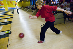 Older woman playing ten pin bowling,