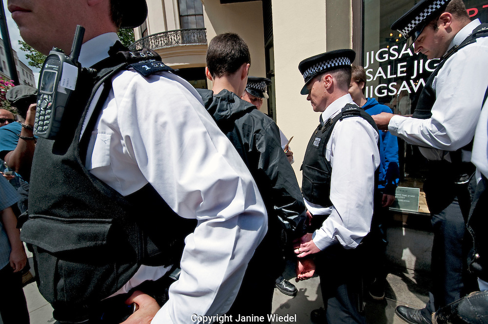 Young boys being stopped and searched by police when on a protest March agains job cuts.