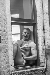 man in briefs sitting on a window ledge in New York City