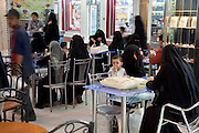 A boy sits with women wearing burqas in a snack and juice bar restaurant in Sanaa, Yemen, adjacent to a shopping mall. Most Yemeni women cover themselves for modesty, in accordance with tradition. (From the book What I Eat: Around the World in 80 Diets.)