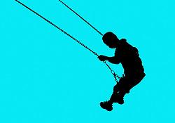 Young boy swinging on playground swing,
