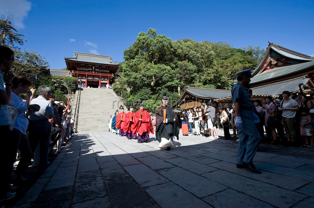 Head priest Shigeho Yoshida leads priests and female maiko attendants on a procession from the main hall following a ritual in the main hall of Tsurugaoka Hachimangu shrine during the second day of the 3-day Reitaisai grand festival in Kamakura, Japan on  15 Sept. 2012.  Photographer: Robert Gilhooly