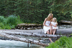 mother and daughter enjoying time together outdoors on a tree trunk in Montana