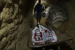 59645970  .A man delivers KFC food in the underground tunnel beneath the Gaza-Egypt border in the southern Gaza Strip city of Rafah on May 15, 2013. Ordering fast food from one of the world s most popular restaurants KFC has become possible in Gaza after Al-Yamama delivery company started to bring the food from the Egyptian north Sinai, which borders Gaza, May 15, 2013. Photo by: imago / i-Images. UK ONLY