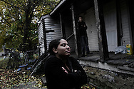 UNITED STATES,  MICHIGAN, DETROIT, October 30, 2012:  A woman and one of her sons, stand in front of their house. Her husband works in a factory that produce tires and leaves with his family in the south part of Detroit, very close to the industrial area. He wish to move from there as crime level in the area vertically increased in the last years. Due to crime, pollution and economic crisis a large number of houses in the area are abandoned. ALESSIO ROMENZI