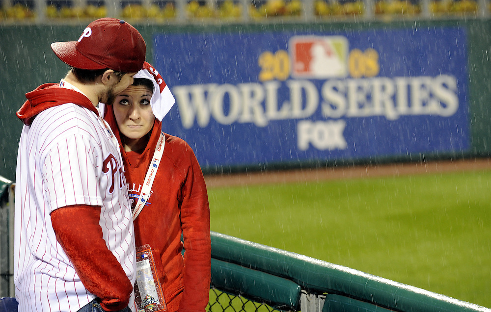 Bobby and Jessica Henning of Coopersburg, Pennsylvania stand near the field as heavy rain falls prior to the scheduled start of game three of the 2008 World Series between the Tampa Bay Rays and the Philadelphia Phillies at Citizens Bank Park in Philadelphia, Pennsylvania, USA 25 October 2008.  The best-of-seven series is tied 1-1.
