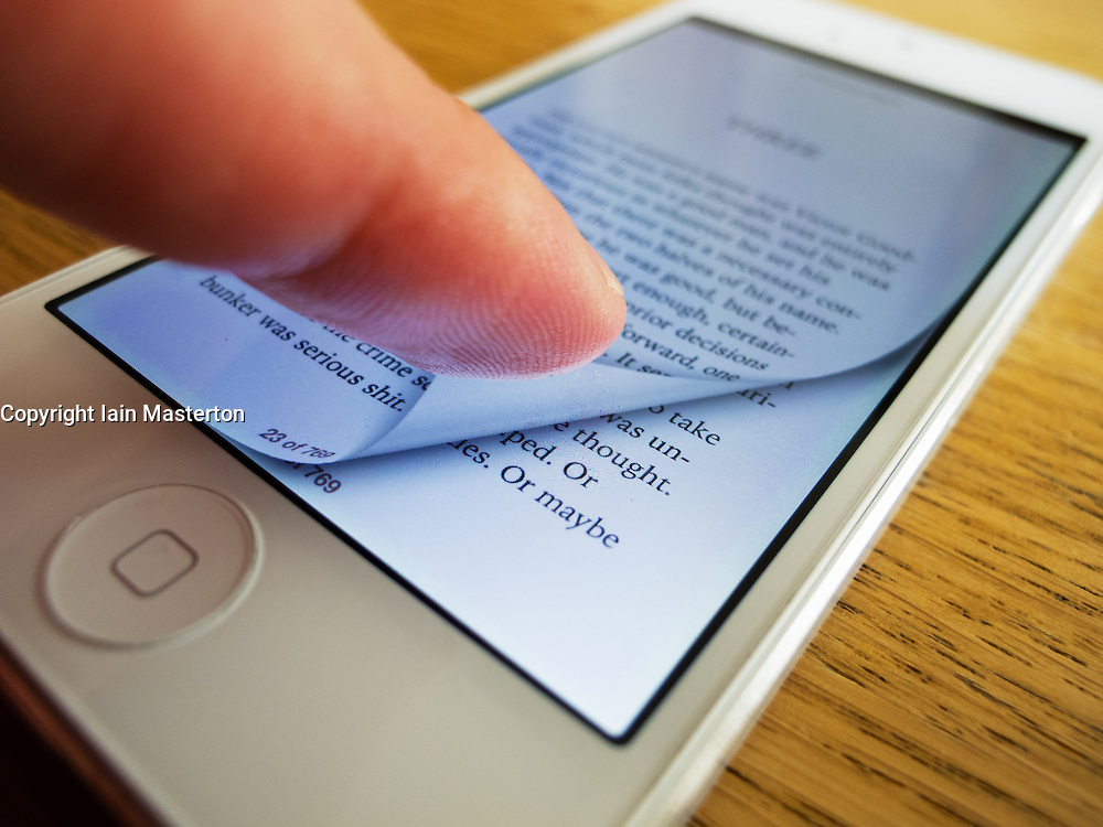 Detail of iPhone 5 smart phone screen showing iBooks e-book reader with page turning