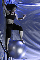 young woman exercising swiss ball studio