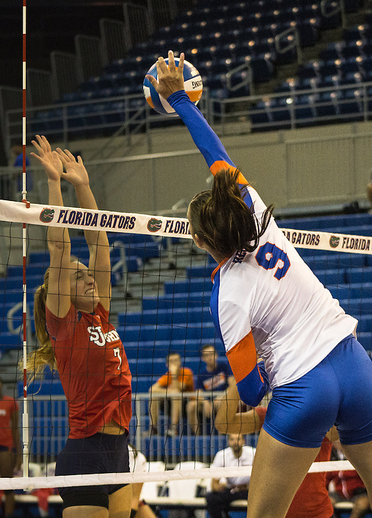 Florida's Živa Recek beats defender Deniz Mutlugil with a powerful spike during the first set of Thursday's night game against St. John's. (photo by Samuel Navarro)
