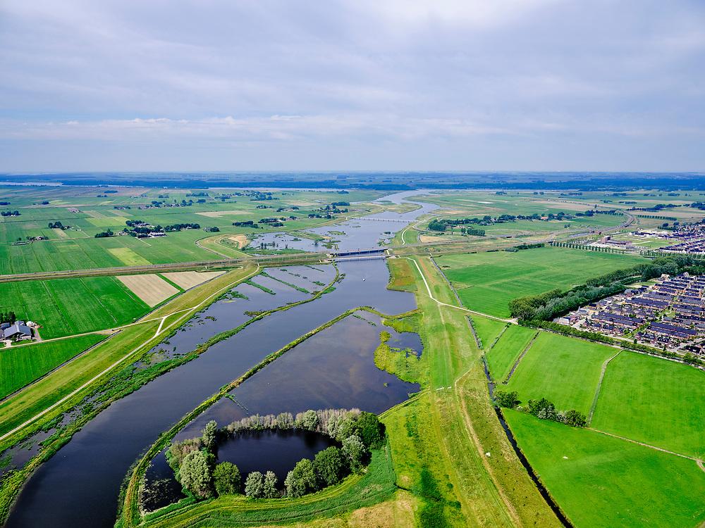 """Nederland, Overijssel, Gemeente Kampen; 21–06-2020; het Reevediep richting monding in het Revemeer (voorheen Drontermeer) met in de voorgrond De Koerskolk. In het midden de Reevediepbrug(rijksweg N50)met parallel deSpoorbrug Reevediep en de Nieuwendijkbrug, Flevoland aan de verre horizon.<br /> Het Reevediep is aangelegd in het kader van het project Ruimte voor de Rivier om bij hoogwater water af te voeren voordat dit het nabij gelegen Kampen bereikt, direct naar het IJsselmeer, de 'bypass Kampen'. Het Reevediepgebied is ook een natuurgebied en vormt een ecologische verbindingszone tussen rivier de IJssel en Drontermeer.<br /> Reevediep towards the outfall in the Revemeer (formerly Drontermeer) with De Koerskolk in the foreground. In the middle the Reevediep Bridge (national road N50) with parallel the Reevediep Railway Bridge and the Nieuwendijk Bridge, Flevoland on the far horizon.<br /> The Reevediep has been constructed as part of the Room for the River project, and functions to discharge high waters before reaching the nearby Kampen, directly to the IJsselmeer, the """"bypass Kampen"""". The Reevediep area is also a nature reserve and forms an ecological connecting zone between the river IJssel and Drontermeer.<br /> <br /> luchtfoto (toeslag op standard tarieven);<br /> aerial photo (additional fee required)<br /> copyright © 2020 foto/photo Siebe Swart"""