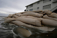 Sand bags are placed to slow beach erosion on Ocean Isle Beach in South Carolina.  Ocean Isle is an example of poor beach management in that it was developed with canals draining wetlands that would otherwise hold storm water and stabilize the beach. Also, homes were built on top of dunes. The Army Corps of Engineers has been renourishing parts of the island to hold back the beach erosion but this section, the easternmost tip of the island, is beyond repair.