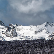 Sawtooth Mountains in winter snow with storm clouds
