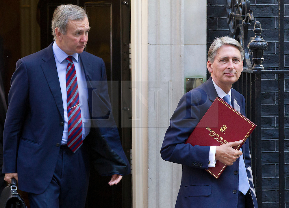 "© Licensed to London News Pictures. 29/08/2013. London, UK. The Defence Secretary Philip Hammond (R) and Chief of Defence Staff General Sir John Nicholas Reynolds Houghton leave a meeting of the British cabinet on Downing Street in London today (29/08/2013) as a recalled British Parliament prepares to debate the possibility of ""direct"" military action over recent reports an alleged chemical weapons attack in Syria. Photo credit: Matt Cetti-Roberts/LNP"