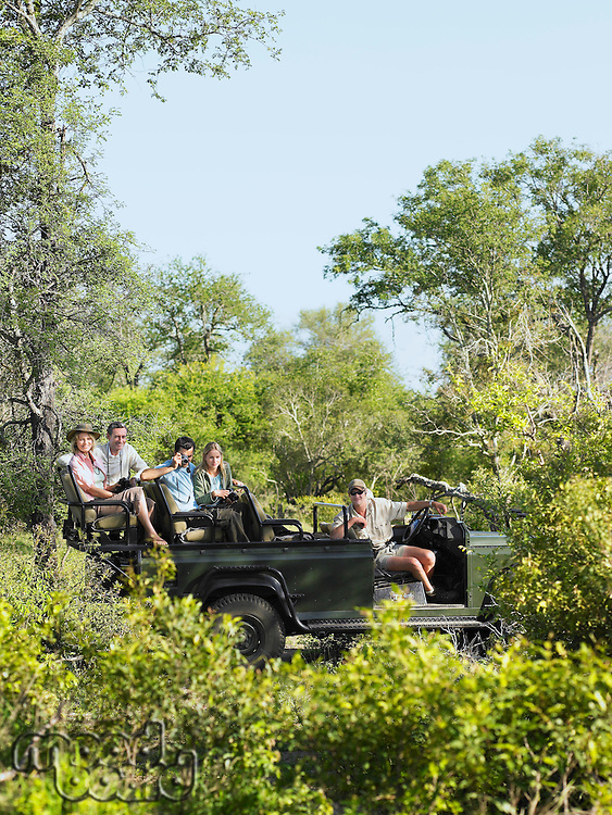 Four tourists and driver in jeep on safari side view