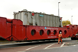 © Licensed to London News Pictures.  03/11/2013.  Warmley, South Gloucestershire.  An electricity transformer, one of the biggest abnormal loads ever transported on the roads is driven through the village of Warmley and onto the Avon ring road, to avoid a weak point in the M4. The giant transformer came from the decommissioned Didcot power station and is being taken to Avonmouth to be shipped abroad.  The load together with the huge transporter, weighed 640 tonnes.  03 November  2013.<br /> Photo credit : Simon Chapman/LNP