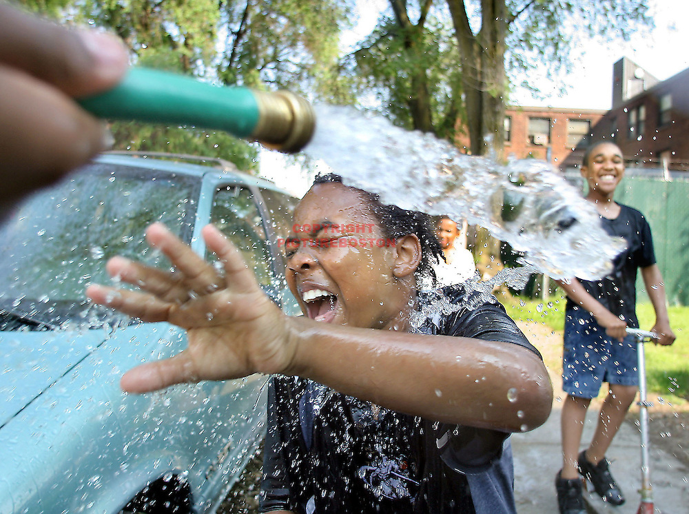 Hot weather weekend comes to an end....but not before 10 yr old Tracy Owens gets splashed by a friend's hose on Rev Burke st in Southie.