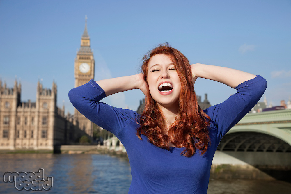Angry young woman with hands on head screaming against Big Ben clock tower, London, UK