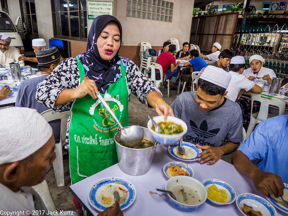 14 JUNE 2017 - BANGKOK, THAILAND: A woman serves beef noodle soup during the Iftar meal at Masjid Hidayatun Islam. Iftar is the evening meal when Muslims end their daily Ramadan fast at sunset. Iftar is a communal event at Masjid Hidayatun Islam and more than a hundred people usually attend the meal.      PHOTO BY JACK KURTZ