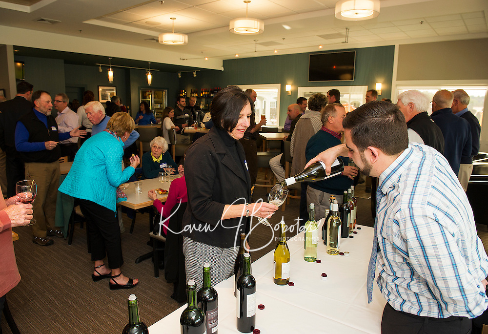 Josh Campo of Pine State Beverages pours a glass of wine for Karen Sullivan at Laconia Country Club's opening reception of their newly renovated bar and restaurant on Thursday evening.  (Karen Bobotas/for the Laconia Daily Sun)