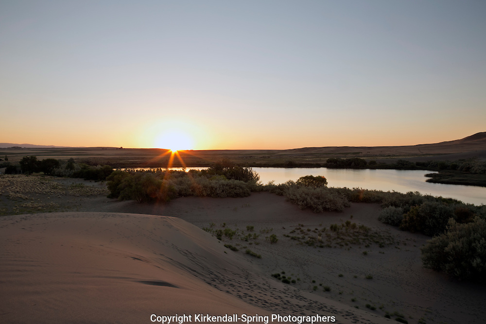 ID00651-00...IDAHO - Sunrise over one of the Dune Lakes at Bruneau Dunes State Park.