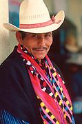 GUATEMALA, HIGHLANDS, MARKETS portrait of Indian man at market wearing traditional textiles in village of Santiago Atitlan on Lake Atitlan