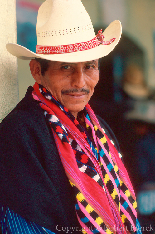 GUATEMALA, HIGHLANDS, MARKETS portrait of Indian man at market wearing traditional textiles in village of Santiago Atitlan on Lake Atitlan