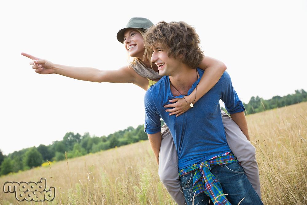 Woman showing something while enjoying piggyback ride on man in field