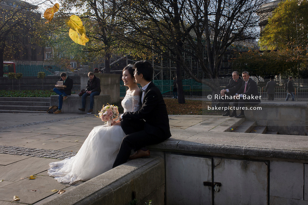A Chinese wedding couple pose for stage-managed potraits in the City of London.