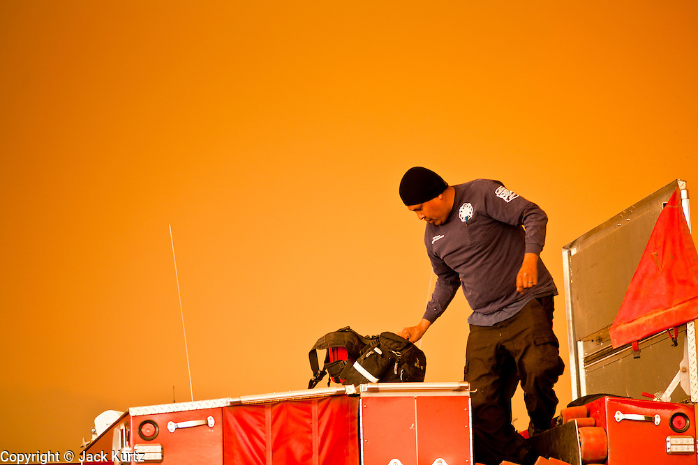 02 JUNE 2011 - ALPINE, AZ: Capt Zelmor Danford (CQ) from White Mountain Apace FD gets his gear out of his type 3 engine at the Wallow Fire near Alpine. Smoke turned the sky a brilliant orange. High winds and temperatures complicated firefighters' efforts to get the blaze under control. Officials have issued a preliminary evacuation order warning residents to be ready to move in the next 12 hours.   PHOTO BY JACK KURTZ