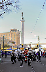 09 February 2016. New Orleans, Louisiana.<br /> Mardi Gras Day. Walking with Skeletons. The Skeleton Krewe meet before sunrise and walk 5 miles from Uptown, making their way along St Charles Avenue and into the French Quarter where they celebrate Mardi Gras Day. The Krewe stopped at Lee Circle for a portrait with the controversial statue of General Robert E Lee. <br /> Photo©; Charlie Varley/varleypix.com