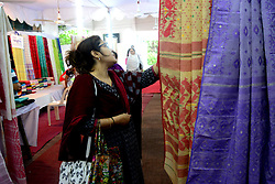 May 25, 2019 - Dhaka, Bangladesh - People visit the Jamdani Sari fair organized by Bangladesh Small and Cottage Industries Corporation (BSCIC) at Shilpakala Academy in Dhaka, Bangladesh, May 25, 2019. The saris, in the price range of BDT 3000-80,000, were in pastel hues as well as shades of bright blue, purple, magenta, among others. Each piece flaunted a unique pattern of the craft. The intricate motifs, meticulously woven by the hard-working jamdani weavers of our country, gave each sari a touch of grandeur and perfection. From the contemporary black-white and black-red combinations, to the classic black, exquisite white and other equally magnificent pieces of the favourite attire of any Bangladeshi woman, the collection was a treat for jamdani enthusiasts. (Credit Image: © Str/NurPhoto via ZUMA Press)
