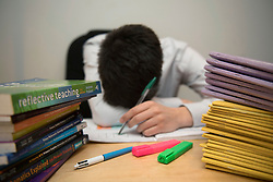 Embargoed to 0001 Monday May 29<br /> File photo dated 05/03/17 of a teacher looking stressed next to piles of classroom books, as teaching is fast becoming a job that is &quot;just too big an ask&quot; with many keen to leave to the profession, an expert has warned.