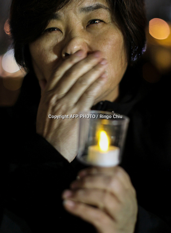 A supporter holds a lit candle during a candlelight vigil in remembrance and support of 'Comfort Women', Japanese military sexual slavery victims during World War II, at Glendale Peace Monument on January 5, 2016 in Glendale, California. AFP PHOTO / Ringo Chiu