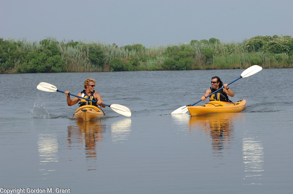 Water Mill, NY - 8/13/05 - Juris Kupris, left, a personal trainer, works with his client, Mike DePaola, right, with kayaks at his clients home in Water Mill, NY August 13, 2005.     (Photo by Gordon M. Grant)<br />