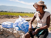 19 NOVEMBER 2010 - PORT-AU-PRINCE, HAITI:  Evame Nelson sells bags of water for about $1 each near a Medicins Sans Frontieres (MSF - Doctors Without Borders) cholera treatment center near the airport in Port-au-Prince. Cite Soleil, a sprawling slum area in PAP is ground zero for the cholera epidemic in the Haitian capital. An outbreak of cholera in northern Haiti about a month ago has spread across the nation. Tens of thousands of people have been hospitalized and treated for cholera and more than 1,100 have died. Cholera is a water borne illness that causes severe diarrhea and death by dehydration in a matter of hours.     PHOTO BY JACK KURTZ    choleraepidemic