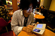 Yuuya Iwama playing the Love Plus dating game on his Nintendo DS in a cafe at Shinjuku area of Tokyo.