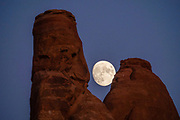 Moonrise at sunset at Devils Garden Campground, Arches National Park, Moab, Utah, USA.